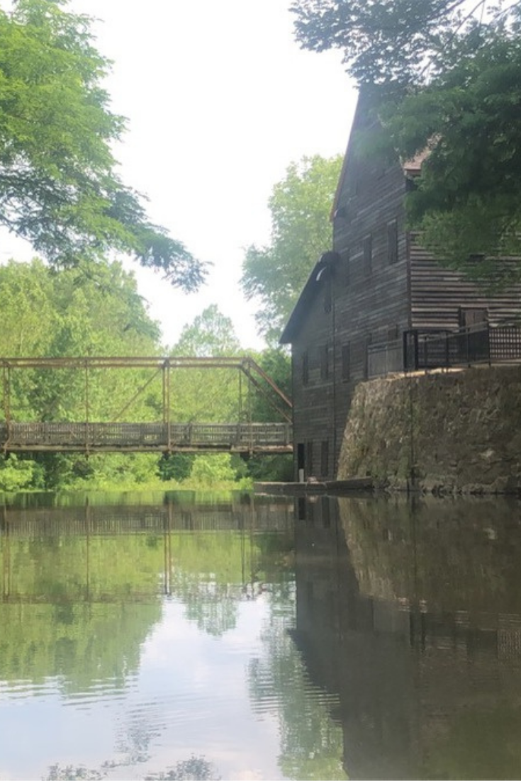 Looking at Pine Mill Bridge and the restored historic Pine Creek Grist Mill over the water of Pine Creek at Wildcat Den State Park