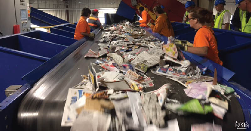 Don't go wishcycling - be sure what you put in the bin is safe to recycle [Image: workers sorting items on a conveyor belt at a recycling center] | Iowa DNR