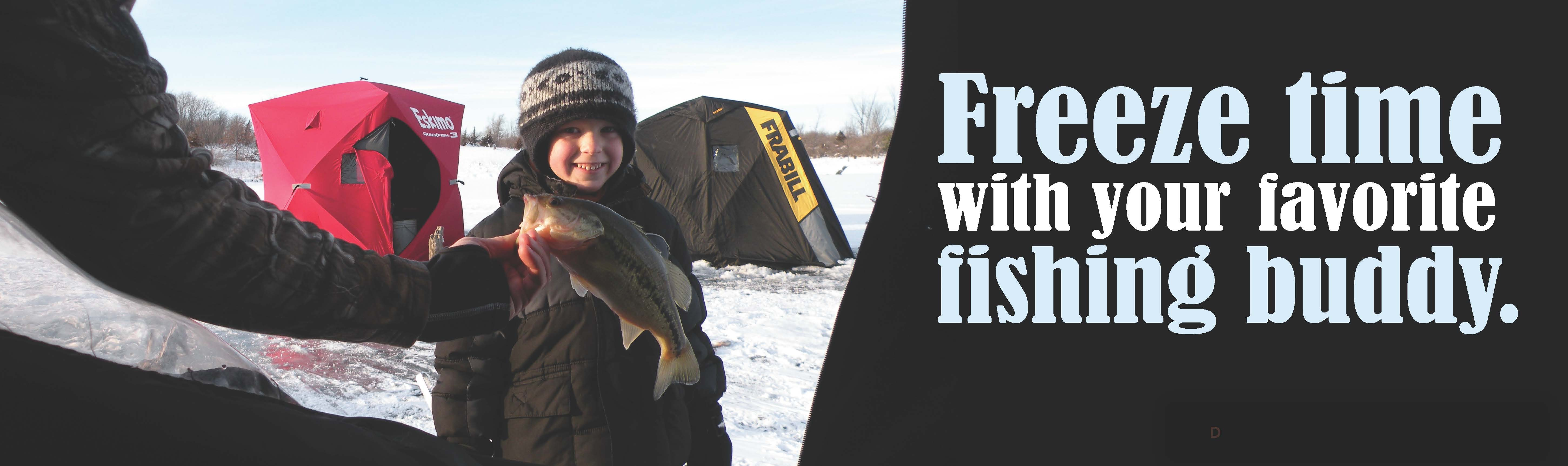 a young boy standing outside an ice fishing shack with a fish.